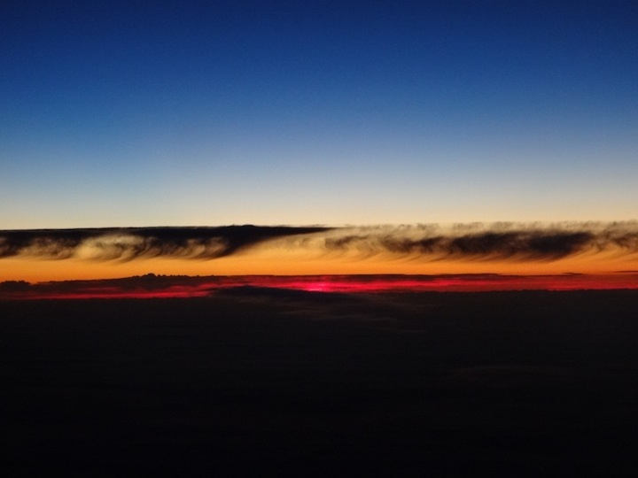 """Photo: Tricia Yamaguchi """"Clouds forming a wave to wash away the fiery sun. From high above."""""""